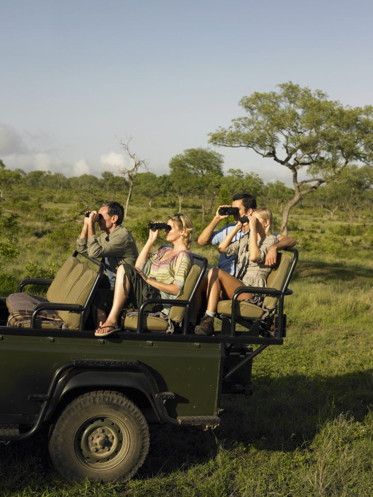 People with binoculars in the heart of Kenya's richest game reserve