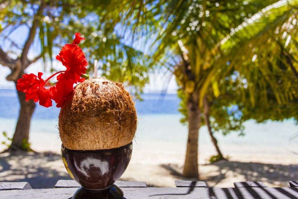 Coconut drink with straw and flower on tropical beach is good any time of the year